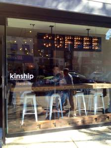 Kinship Coffee's cheerful sign welcomes you on Steinway Street
